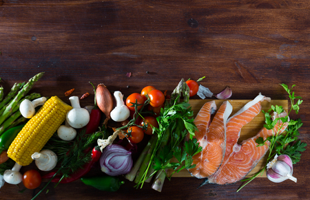 Fresh red fish, vegetables and greens on wooden background, with copyspace. Healthy food concept