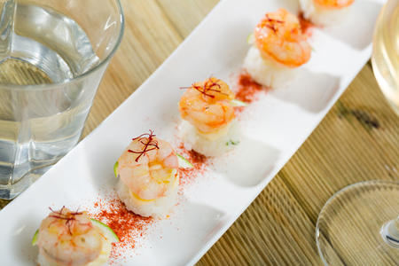 Delicious grilled shrimps served on rice balls with lime garnished with dried saffron threads
