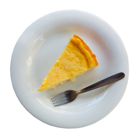 Slice of spanish cheesecake Tarta de queso on white plate. Isolated over white background