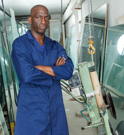 Experienced African American glazier controlling quality of sheet glass in workroom Reklamní fotografie