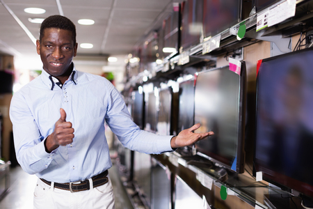Satisfied pleasant smiling male choosing televisor in  household appliances store