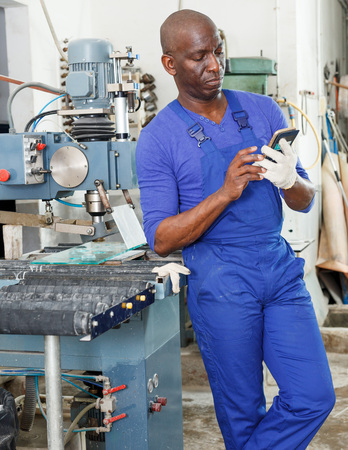 Serious African American worker of glass workshop using mobile phone while standing near glass processing machine