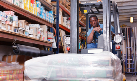 African American positive diligent worker of building materials warehouse working on forklift truck