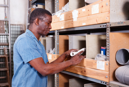 African-American  positive  man choosing materials for overhauls in building materials store