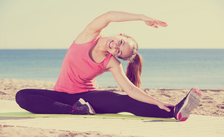 Pretty sporty woman exercising yoga at sea beach