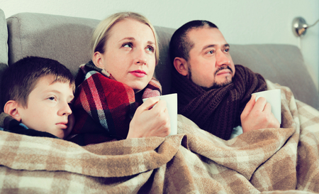 Young family with son catching cold, wrapping in blanket