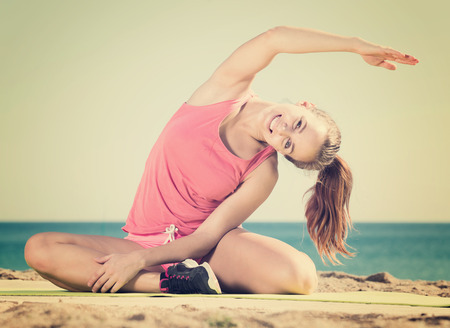sports young woman exercising on exercise mat outdoor at the seaside