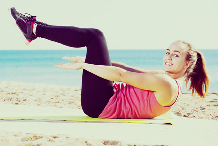 Young smiling girl doing yoga at seaside on a sunny day
