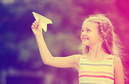 smiling girl in bright dress playing with flying paper airplane toy outdoors