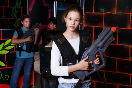 Portrait of teenager girl with laser pistol posing in laser tag labyrinth on background with her team