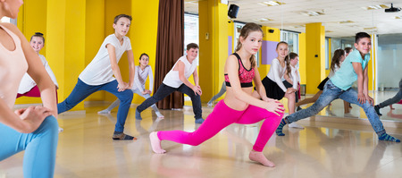 Children dancing synchronous group choreography with female coach at the dance hall
