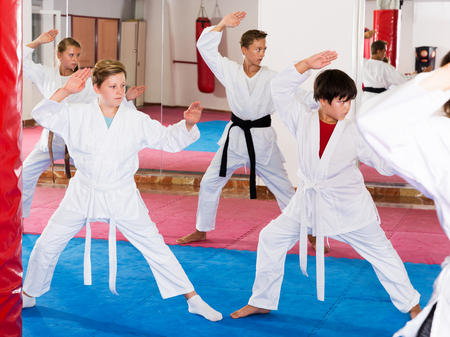 sportive kids in kimonos practicing effective karate techniques in group workout at training room