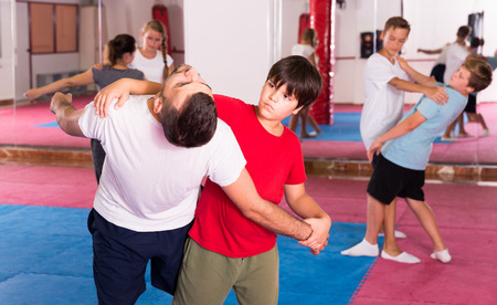 Mixed age group at self protection workout, training attack movements in pairs
