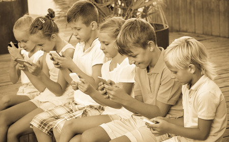 Busy glad children holding smartphones in hands and sitting together outdoors