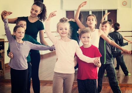 Happy little boys and beautiful girls having dancing class and their teacher 免版税图像