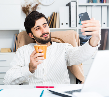 Cheerful young office worker taking selfie on his smartphone at desk  in modern office