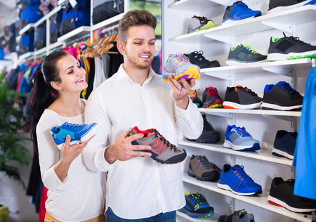 Young american loving couple deciding on new sneakers in sports store