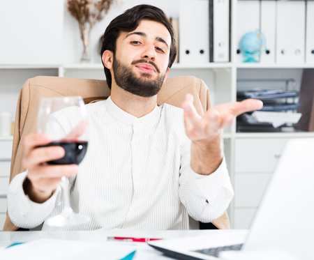 Handsome young office worker drinking red wine at office desk