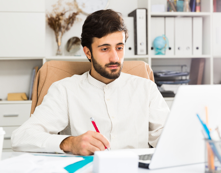 Young confident office worker working at laptop in modern office Banco de Imagens