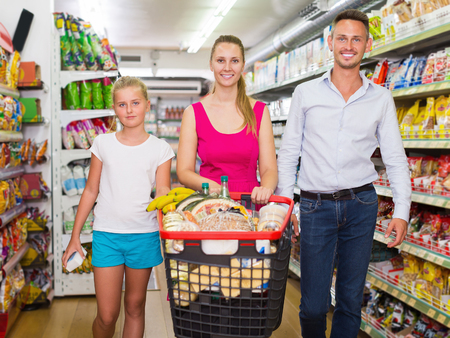 Young family smiling and standing with purchases in shopping cart in market