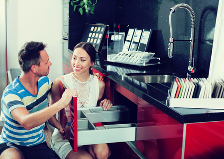 Young man and woman choosing furniture fittings for drawers in kitchen furnishing store