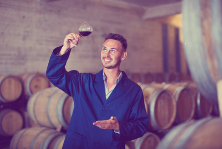 Male young diligent winemaker in uniform having glass of wine in hands in cellar