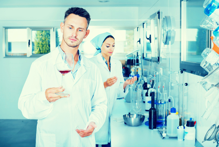 Young man in white coat checking wine acidity and sugar saturation in chemical laboratory on the winery