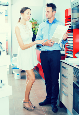 Young woman choosing material for facades for kitchen furniture with seller