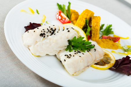Steamed cod fillets served with corn, cherry tomatoes, parsley and lemon. Recipe: cod 250g simmer in pan with water and olive oil for 10 minutes, add spices to taste, garnish with vegetables