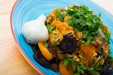 Oriental cuisine - pilaf with lamb, dried plums and apricots, saffron and sweet garlic
