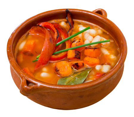 Bulgarian cuisine. Bob chorba - delicious spicy bean pottage with pepper, carrots and tomatoes in clay soup bowl.  Isolated over white background