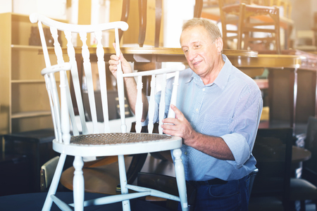 Smiling adult man is buying antique furniture for home in store
