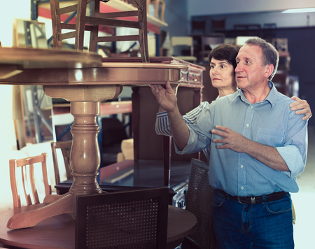 Smiling adult woman with her husband are buying antique table for home in store