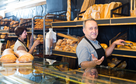 Portrait of glad mature bakers with fresh bread smiling in bakery