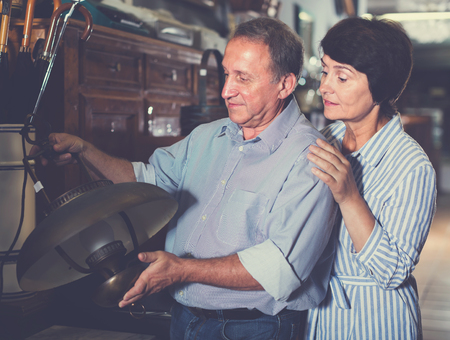 mature couple is shopping the old lamp for home in the antique store