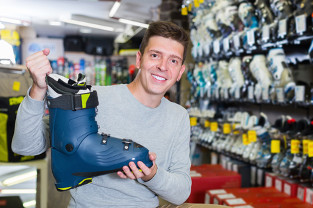 Customer young man is trying on new boots for skiing in store