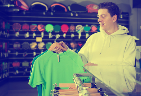 Young man is buying T-shirt for tennis in the speciality store.