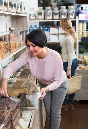 Joyful young and mature women picking nuts and dried fruits sold by weight in organic store Banco de Imagens