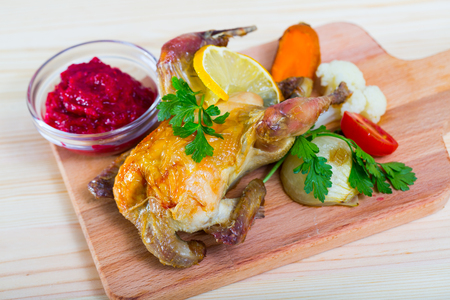 Delicious grilled hen served on wooden board with cranberry sauce and broiled vegetables Imagens