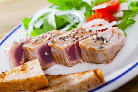 Delicious slightly fried tuna sprinkled with sesame served on plate with toasts, fresh tomatoes and greens