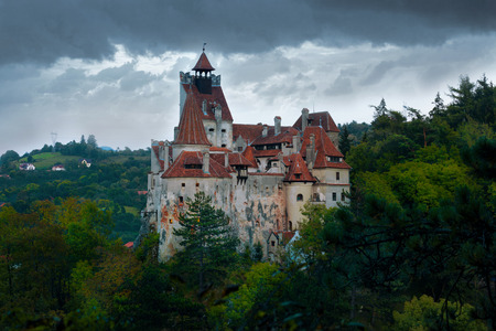 View of Bran Castle on cliff top on background of thunderclouds, Romania