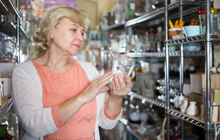 customer woman choosing crystal glass for wine in the dishes shop