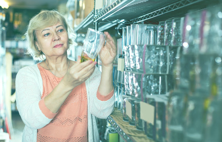 aged customer woman choosing glass for drink in the dishes shop