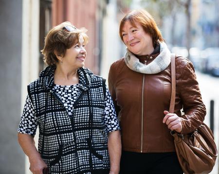 Couple of mature women enjoying a city walk and smiling