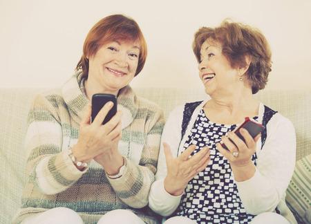Smiling positive mature women browsing internet on smarthphones indoor