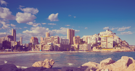 sunny sandy beaches of Benidorm with modern housing and mountains on background Stock Photo