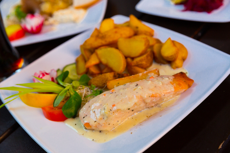 Image of salmon with sauce and potatoes on the plate indoors.