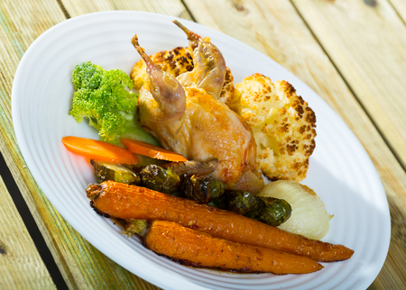 Delicious poultry dish - partridge baked with vegetables in honey-mustard sauce