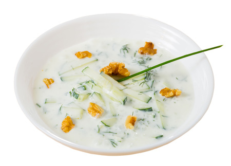 Middle East traditional summer dish Tarator, chilled vegetable soup with yogurt, cucumbers, greens, walnuts. Isolated over white background Zdjęcie Seryjne