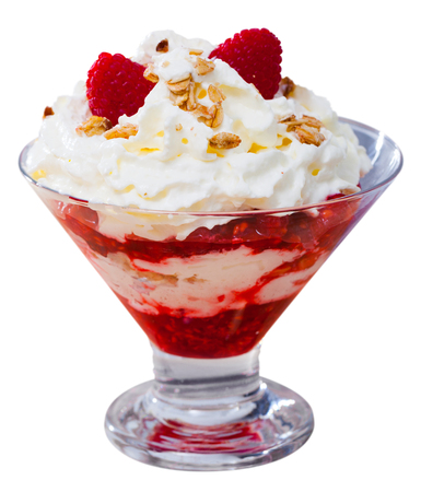 Cranachan – traditional scottish dessert.  Whipped cream with berries and oatmeal served in glass. Isolated over white background